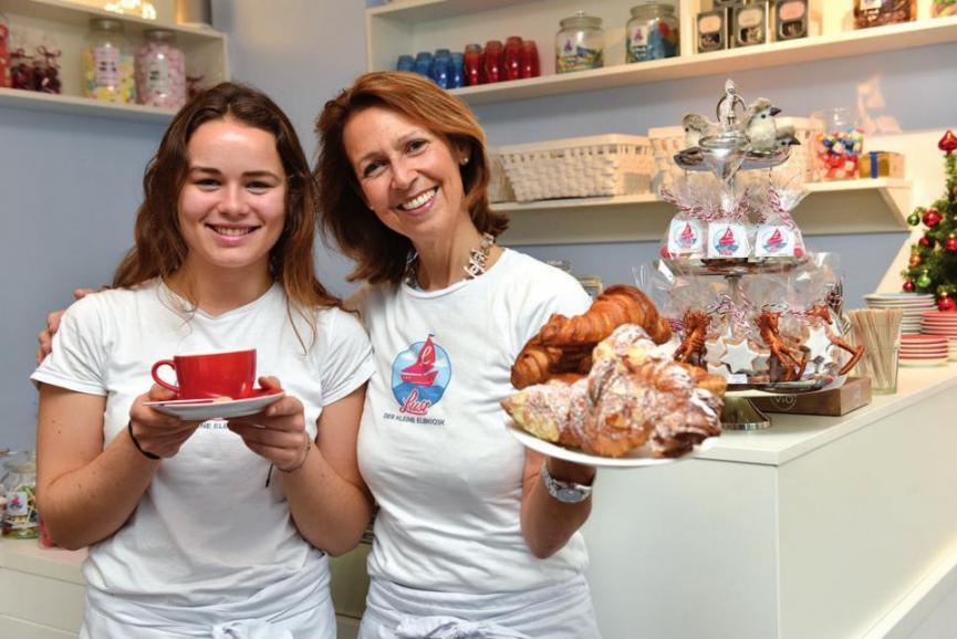 Café-Chefin Katharina Wolter (rechts), Mitarbeiterin Stella Wein bieten neben Croissants und kleinen Köstlichkeiten auch Präsente wie Wein und Schokolade