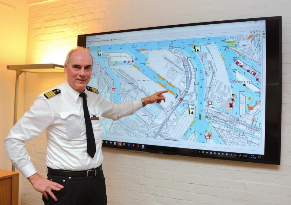 Hafenkapitän Pollmann vor einer digitalen Seekarte, die Teile des Hamburger Hafens zeigt.