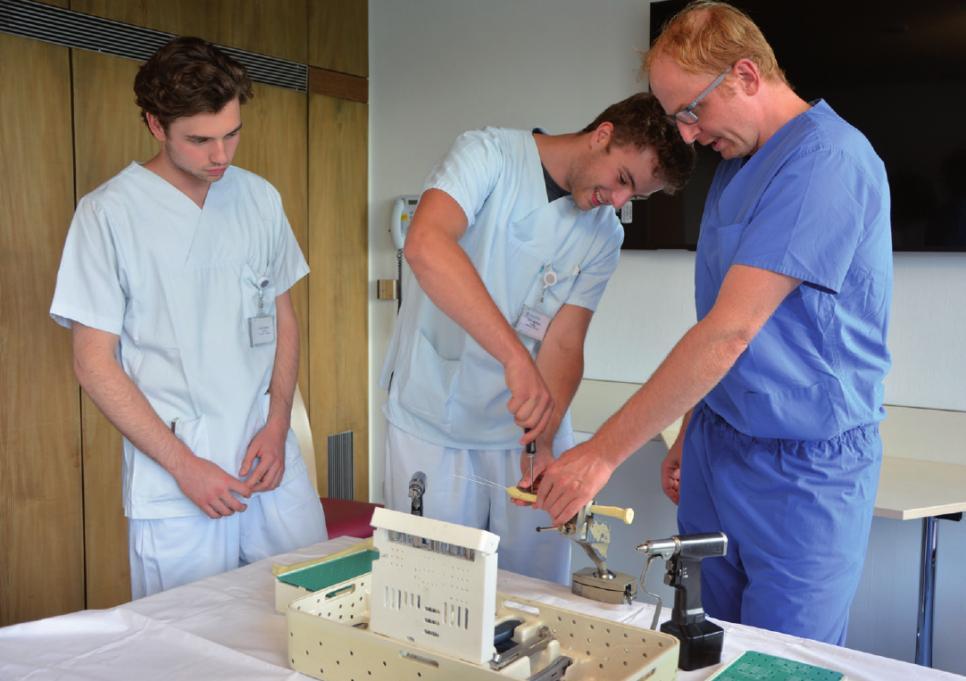 Linus Rehse und Leon Kehler lernen von Chefarzt Prof. Dr. Lars Gerhard Großterlinden, wie ein gebrochener Unterarmknochen mit einer Platte stabilisiert wird