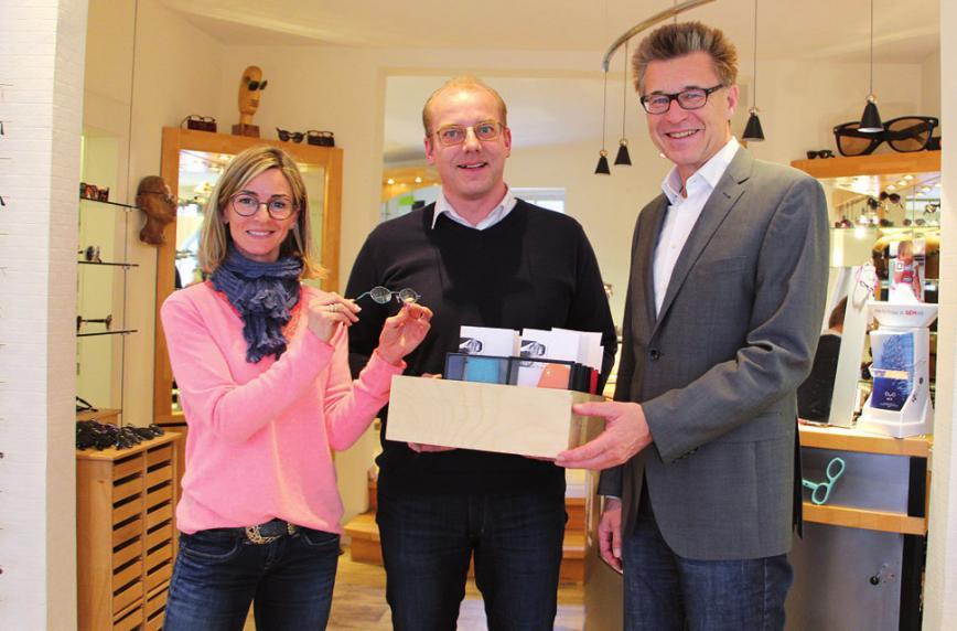 Ulrike Rother und Sven Hartmann vom Brillenhaus Blankenese überreichen Augenarzt Dr. Kaupke gespendete Kinderbrillen