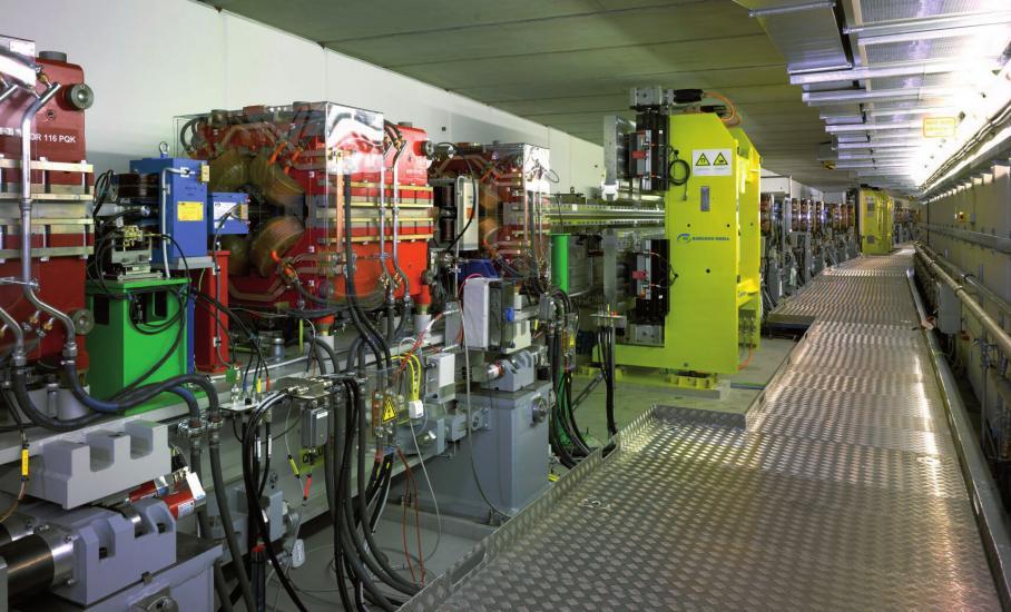 Blick entlang des Speicherrings PETRA III mit Ablenkmagneten (blau), Fokussiermagneten (rot) und Undulatoren (gelb) im Bereich der Experimentierhalle FOTO: DESY 2009
